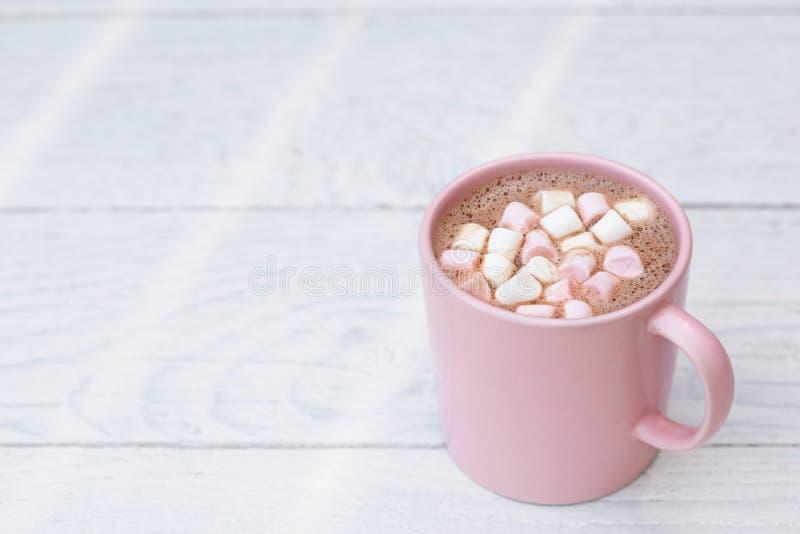 Gorąca czekolada z małymi różowymi i białymi marshmallows w różowym ceramicznym kubku na bielu malował drewno Przestrze? dla teks zdjęcia stock
