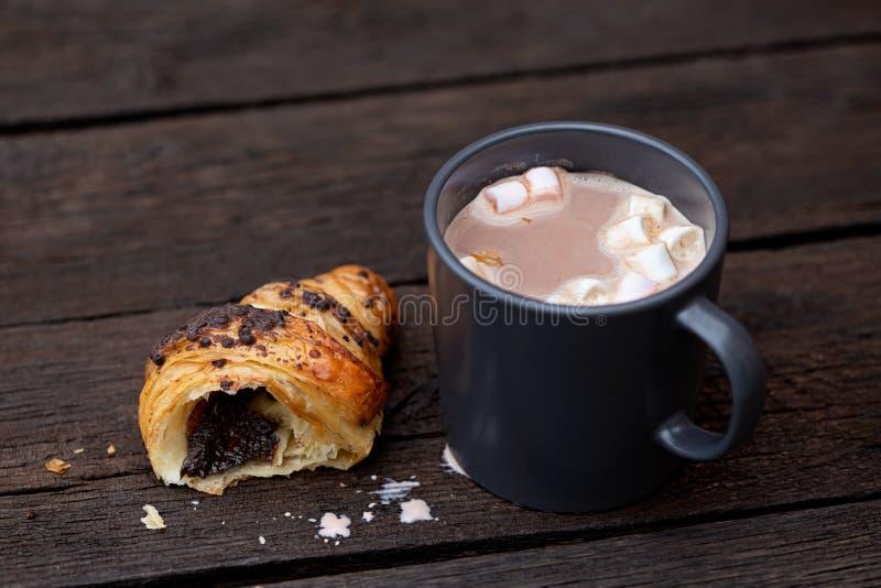 Gorąca czekolada z marshmallows w niebieskoszarym ceramicznym kubku obok połówki odizolowywającej na nieociosanym ciemnym brązie  zdjęcie royalty free