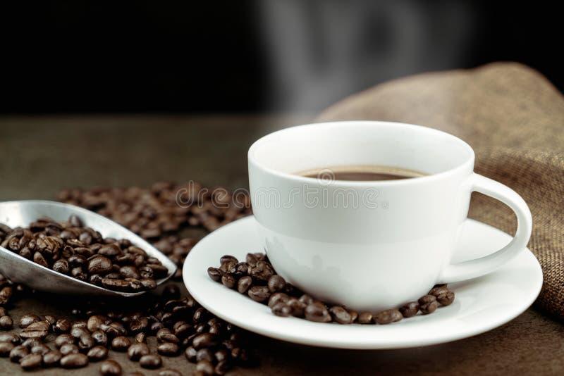 Gorąca kawa w białej filiżance z pieczonymi kawowymi fasolami, torbą i miarką na kamienia stole w czarnym tle, obrazy stock