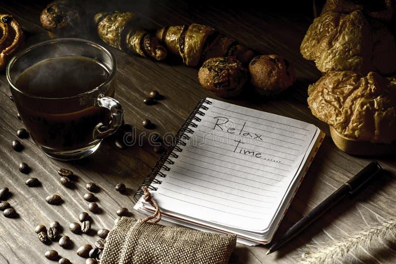 Gorąca kawa w białej filiżance z piekarnią i kawowymi fasolami w konopianej torbie z notatnikiem umieszczającym na ciemnego brązu zdjęcia royalty free