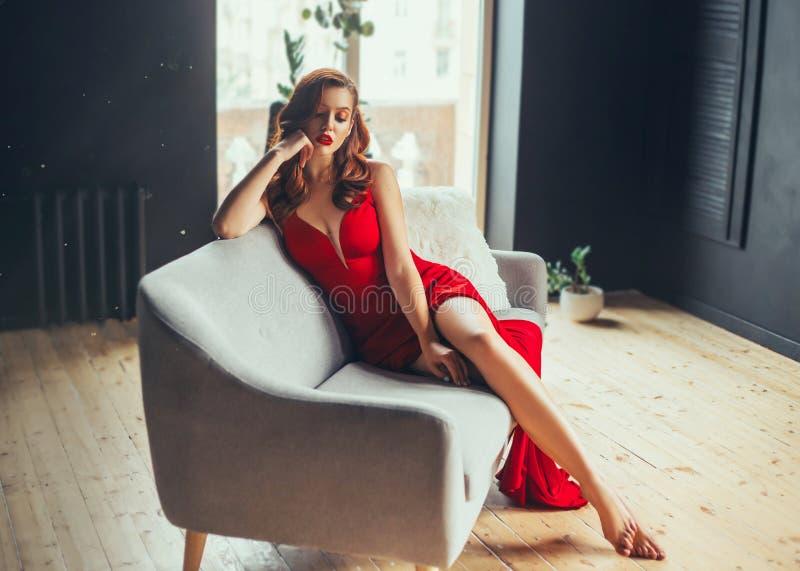 Gorąca młoda kobieta, ubierająca w długiej szkarłatnej czerwieni sukni długo, seksualnie pokazuje jej nagie nogi w loft siedzi na zdjęcie stock