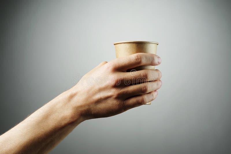 Gorąca napój herbata w naturalnym papierowym szkle na świetle lub kawa - szary tło rozciąga mężczyzny ręką zdjęcia royalty free