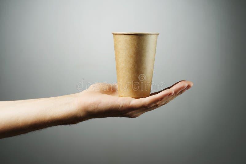 Gorąca napój herbata w naturalnym papierowym szkle na świetle lub kawa - szary tło rozciąga mężczyzny ręką zdjęcie stock