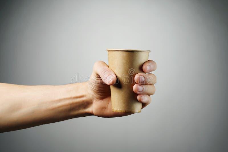 Gorąca napój herbata w naturalnym papierowym szkle na świetle lub kawa - szary tło rozciąga mężczyzny ręką zdjęcie royalty free