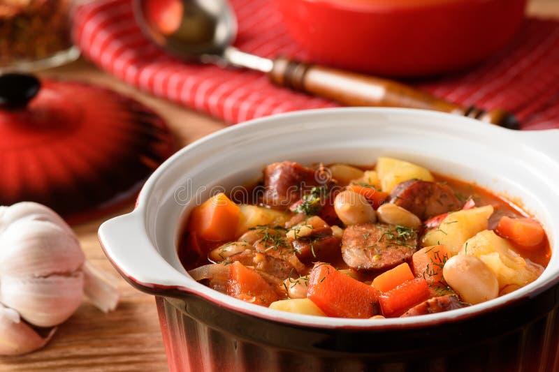 Gorąca polewka z warzywami, uwędzonymi kiełbasami i fasolą, zdjęcia stock