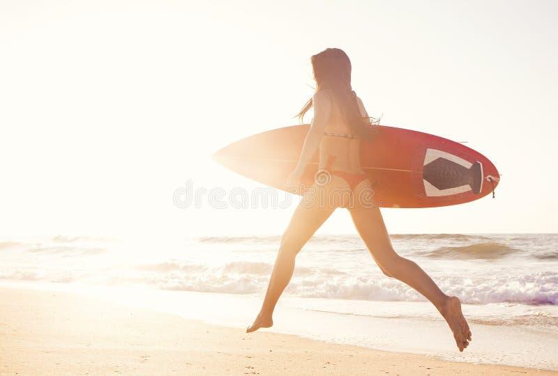 Gorąca surfingowiec dziewczyna przy zmierzchem obrazy royalty free