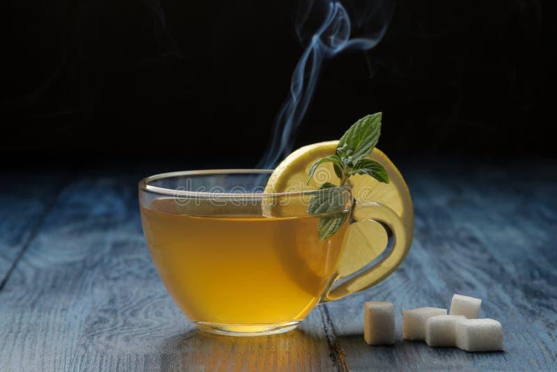 Gorąca zielona herbata z cynamonem, mennicą i cytryną obok cukieru na błękitnym drewnianym stole, zdjęcie royalty free
