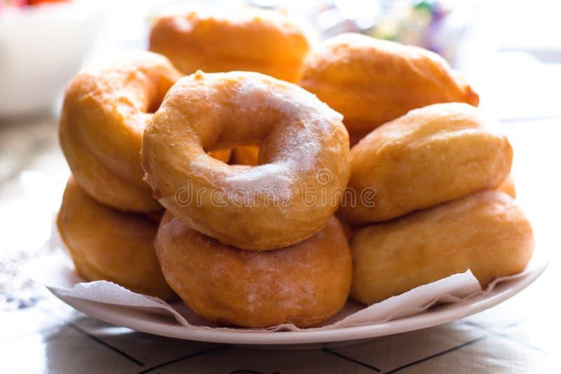 Gorące cukierniczki właśnie kropili z sproszkowanym cukierem, skazywali i rozkładali na naczyniach i zdjęcie royalty free
