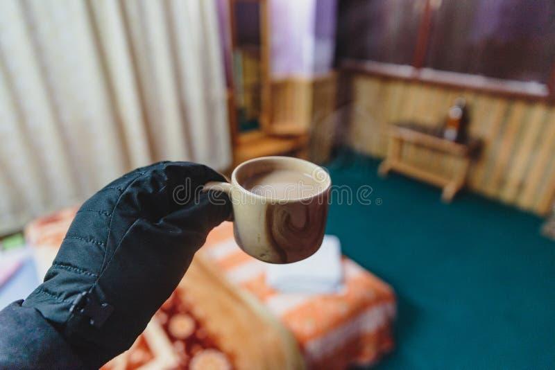 Gorącego tybetańczyka mleka herbaciany chwyt z czarną gloved lewą ręką w marznięcia zimnym tempurature 1 stopnie celsjusza w nocy obrazy stock
