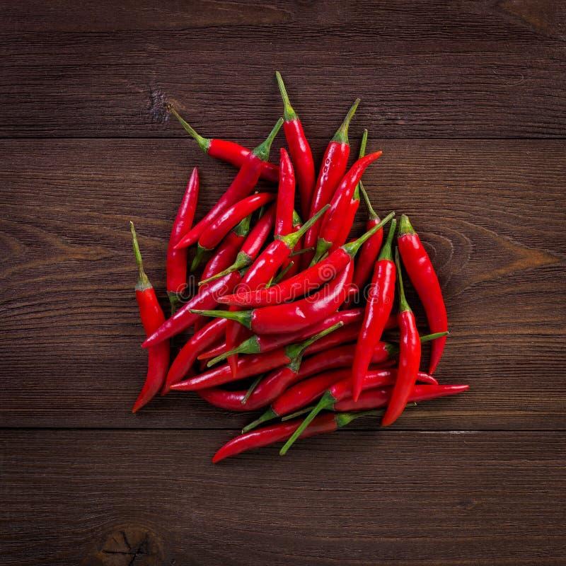 Gorący chili pieprz na ciemnym drewnianym tle, odgórny widok obraz stock