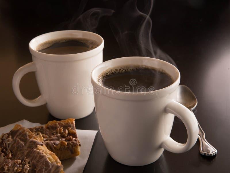 Gorący filiżanka kawy z duńskim na ciemnym tle obraz stock