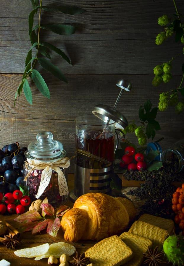 Gorący herbaciany dzbanek na drewnianym tle otaczającym jesieni owoc fotografia stock