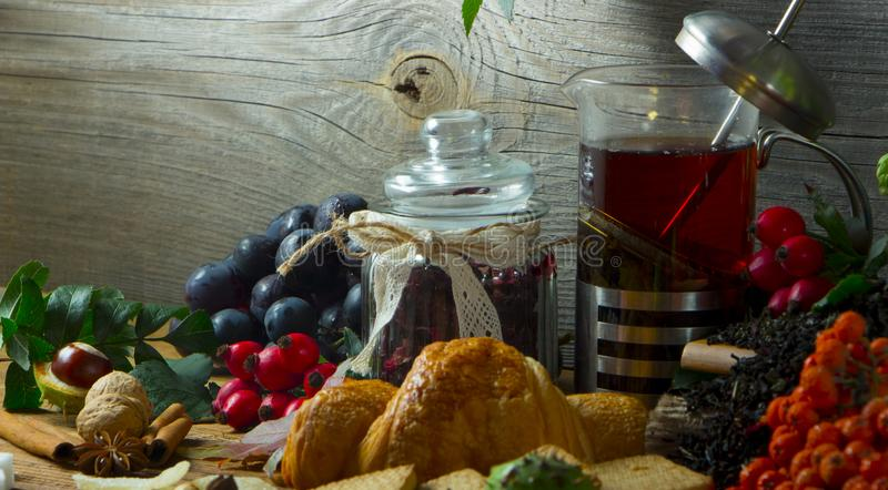 Gorący herbaciany dzbanek na drewnianym tle otaczającym jesieni owoc obrazy royalty free