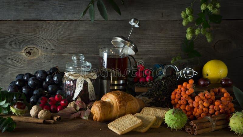 Gorący herbaciany dzbanek na drewnianym tle otaczającym jesieni owoc zdjęcie stock