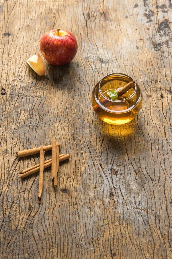 Gorący jabłczany sok w szkle z cynamonem na starym drewnie fotografia royalty free