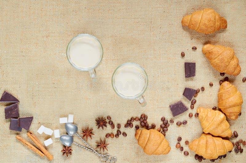 Gorący latte lub kawa w szkłach z kawowymi fasolami, croissants, czekoladą, pikantność i rocznik łyżkami na brown płótnie, obraz royalty free