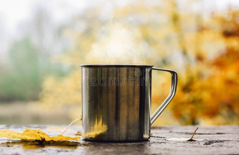 Gorący napój w stalowej filiżance na drewnianym stole Jesieni pomara?cze li?cie zdjęcia royalty free