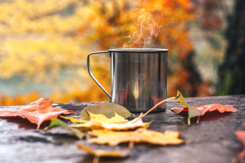 Gorący napój w stalowej filiżance na drewnianym stole Jesieni pomara?cze li?cie obrazy royalty free