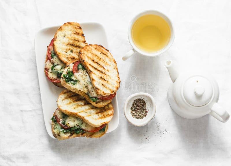 Gorący piec na grillu pomidory, szpinak, mozzarella kanapki i zielona herbata, - zdrowy śniadanie, przekąska na lekkim tle fotografia stock