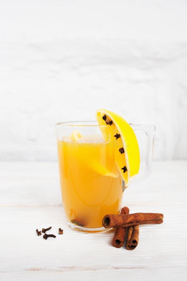 Gorący sok pomarańczowy w szkle i pikantności na bielu zdjęcia royalty free