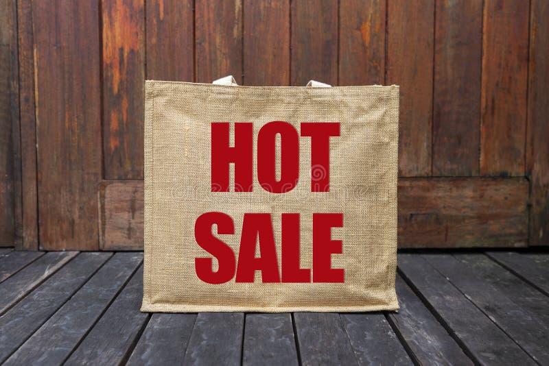 Gorący sprzedaż logo na jutowej torbie na drewnianej podłoga zdjęcia royalty free