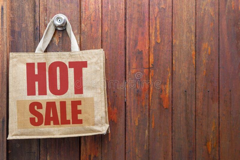Gorący sprzedaż logo na jutowym torba na zakupy wiesza nad starym drewnianym drzwiowym tłem zdjęcie royalty free