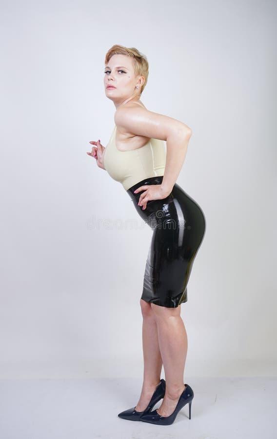 Gor?ca kr?tkiego w?osy blondynki dziewczyna z curvy cia?em jest ubranym lateksow? gumy sukni? na bia?ym pracownianym tle zdjęcia royalty free