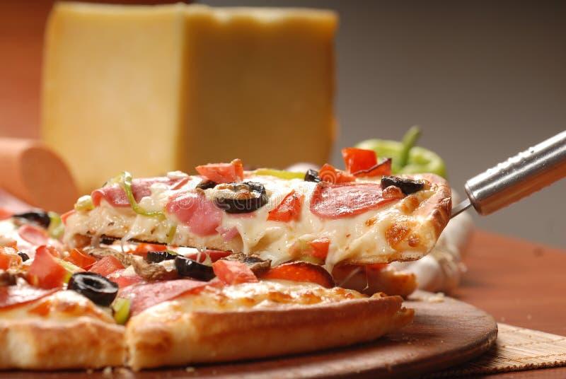 Gor?cy pizza plasterek z roztapiaj?cym serem na nieociosanym drewnianym stole fotografia stock