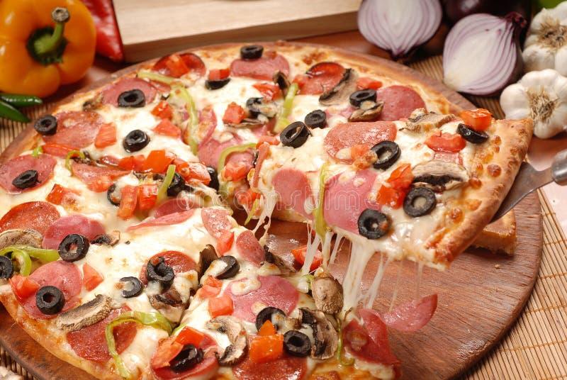 Gor?cy pizza plasterek z roztapiaj?cym serem na nieociosanym drewnianym stole obraz royalty free