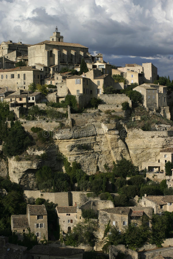 Gordes villages in The Luberon, South eastern France. A moody cloudy sky, the village on two levels showing the cliff face and church stock image