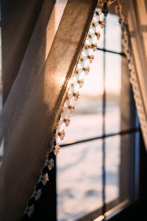Gordijn op het venster waarin de heldere de winterzon glanst stock foto
