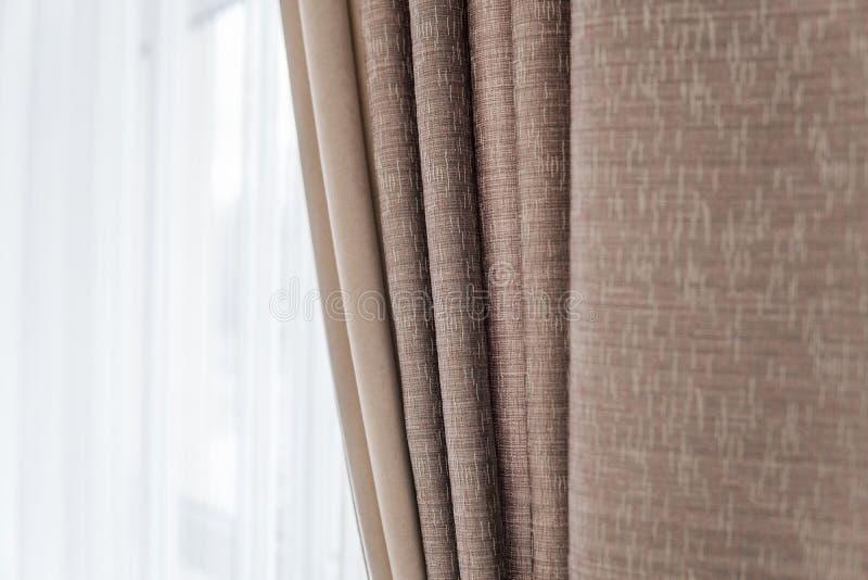 Gordijn tegen venster met een warm zonlicht stock afbeeldingen
