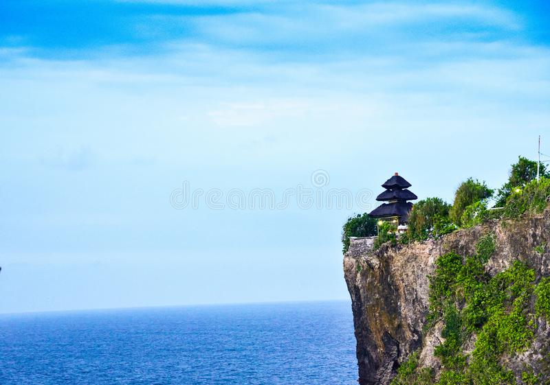 Goregeous romantic sunset at the cliff on top of the mountain with sacred temple on top royalty free stock images
