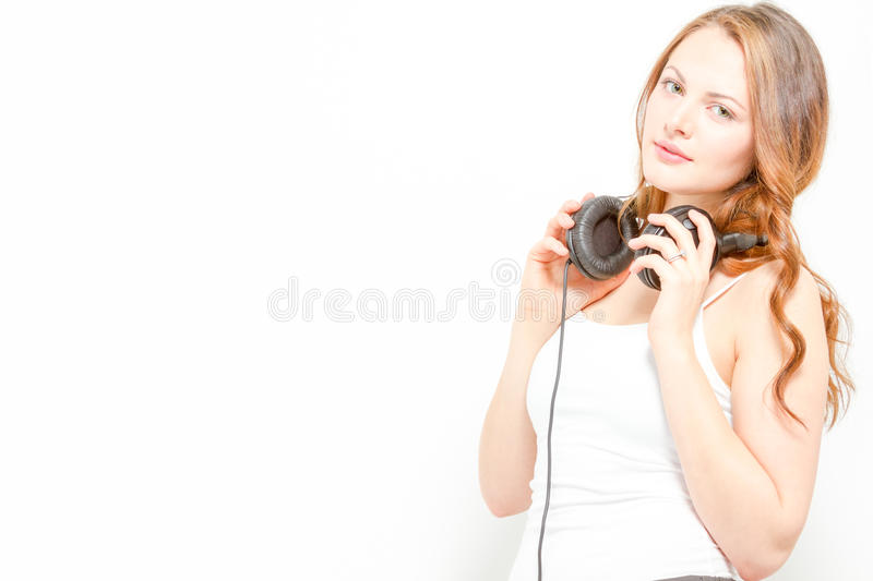 Gorgeous young female with soft smile holds headph stock photography
