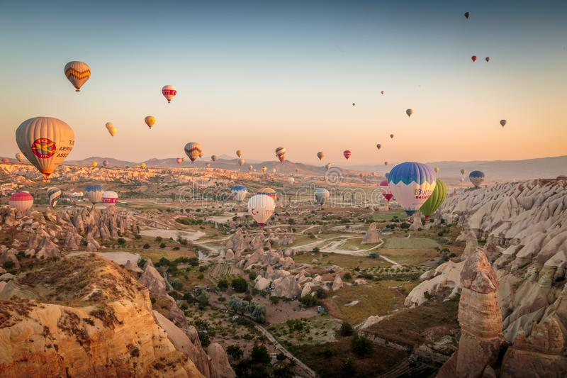 Goreme,卡帕多细亚,土耳其- 2018年6月10日, :五颜六色的热空气看法迅速增加飞行在日出的红色谷 库存照片