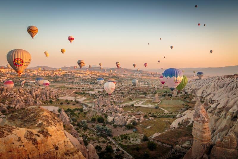 Goreme, Cappadocia, Turchia - 10 giugno 2018: vista delle mongolfiere variopinte che sorvolano la valle rossa su alba fotografie stock