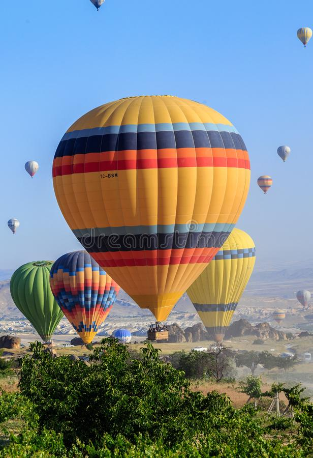 Goreme, Cappadocia, Turkey - 10 June, 2018: view of colorful hot air balloons flying over the Red valley on sunrise royalty free stock images