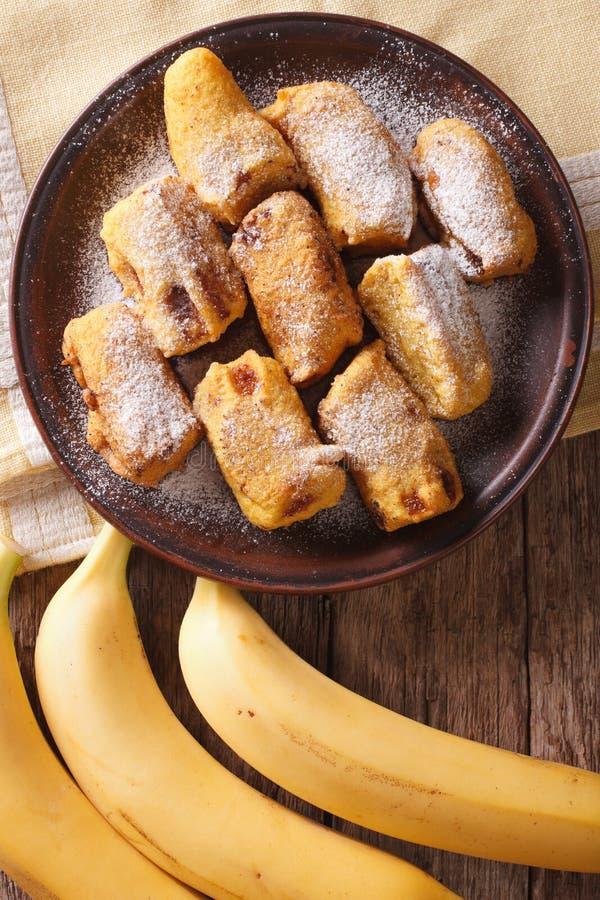 Goreng Pisang зажарило бананы в бэттере на макросе плиты вертикально стоковые фотографии rf