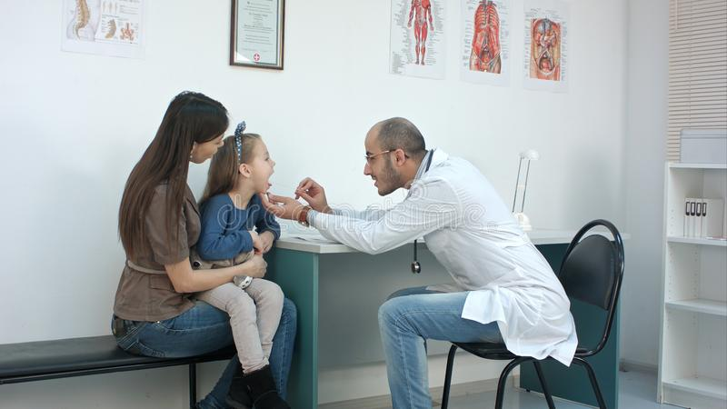 Gorge de examen de pédiatre masculin de petite fille se reposant avec sa mère image libre de droits
