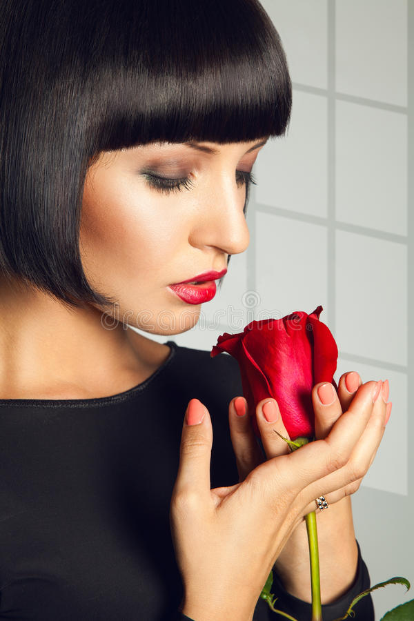Gorgeous adult brunette with red rose on gray background royalty free stock photo