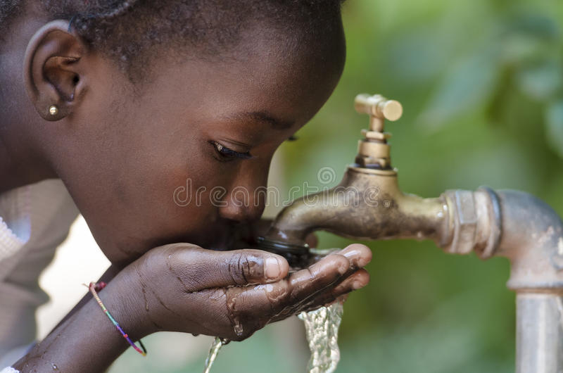 Gorgeous African Black Girl Drinking with Hands Cupped Drought. Clean Fresh Water Scarcity Symbol: Black Girl Drinking from Tap. Young African girl drinking stock images