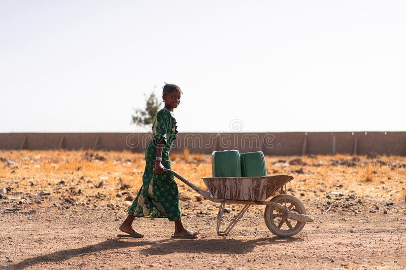Gorgeous African ethnicity Girl Carrying fresh Water for an aridity concept. Candid photo in a village outdoors of Bamako, Mali stock image