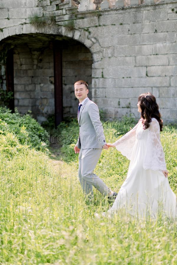 Gorgeous asian wedding couple holding hands walking on a background of the old castle. very lucky in love wedding day. royalty free stock images