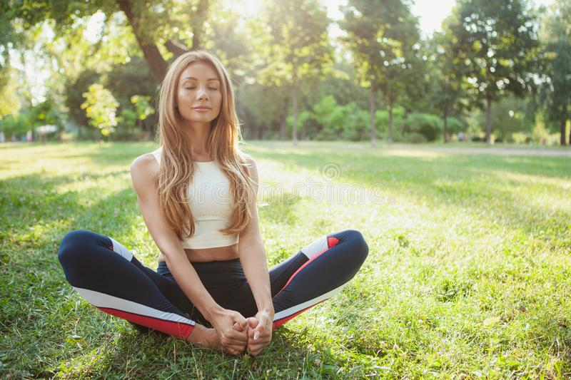 Gorgeous athletic woman doing yoga at the park stock photography