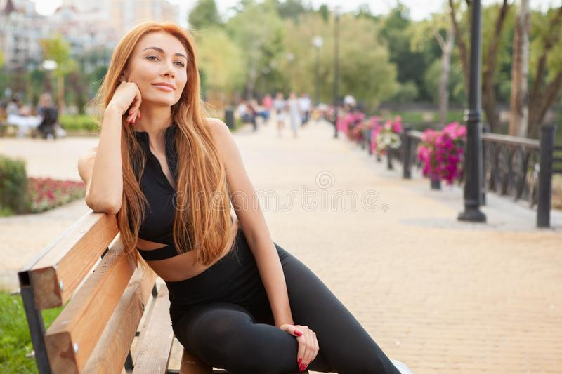 Beautiful fit woman resting outdoors after morning workout royalty free stock image