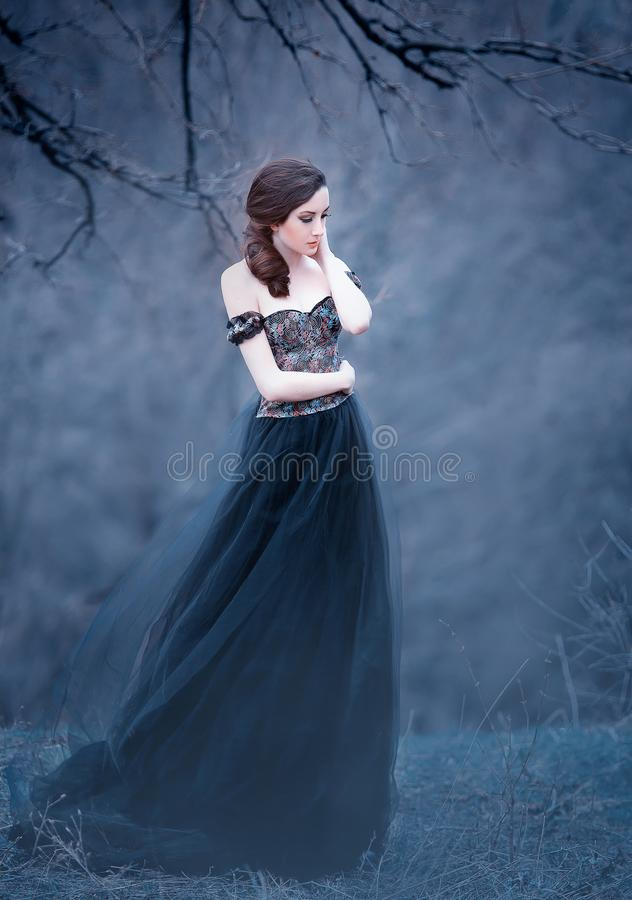 Gorgeous attractive brunette, lady in a long black dress with bare open arms and shoulders, the girl alone in the autumn. Cold forest, the weather in November royalty free stock images