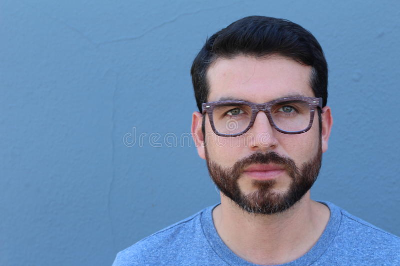 Gorgeous bearded guy wearing glasses leaning on blue wall with copy space. Gorgeous guy wearing glasses leaning on blue wall with copy space royalty free stock photos