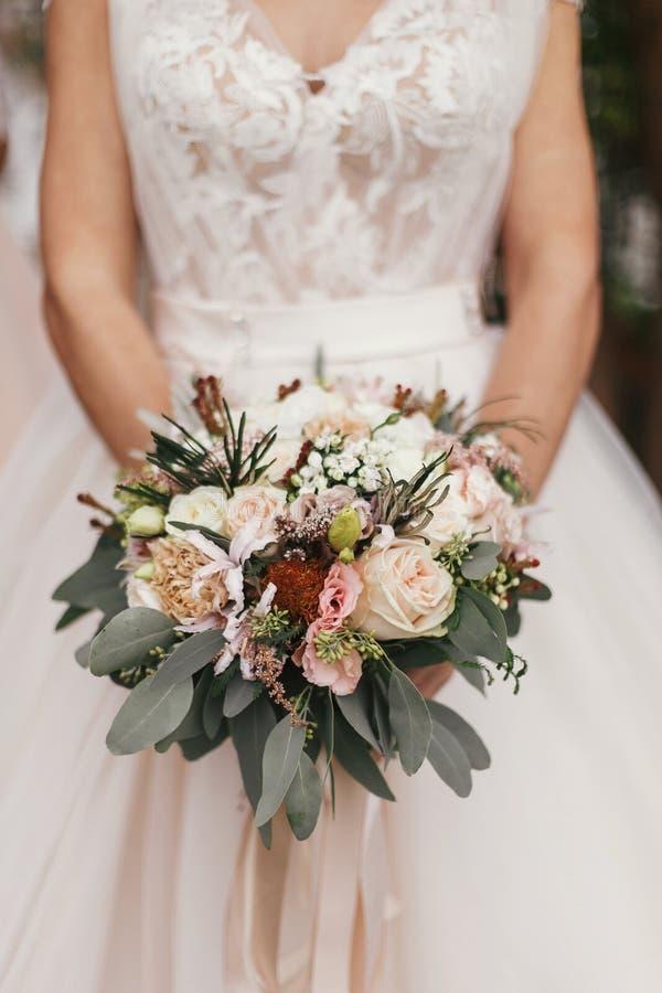 Gorgeous beautiful bride holding stylish wedding bouquet on back stock image