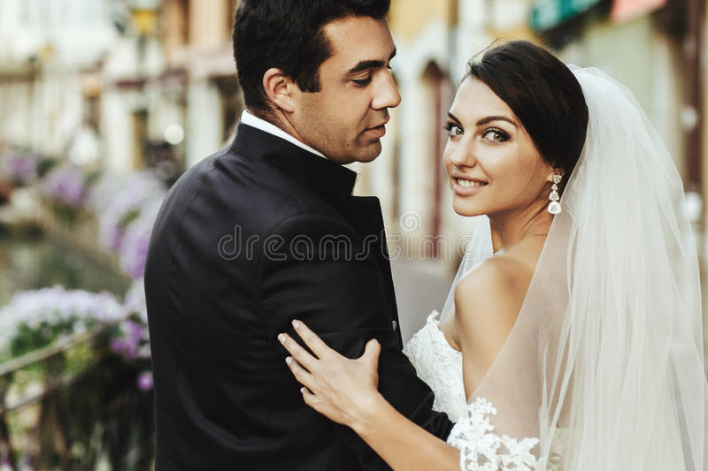 Gorgeous beautiful exotic brunette bride and handsome groom posing closeup stock photography