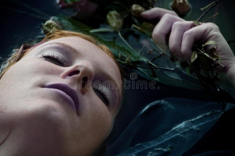 Gorgeous beautiful portrait of a young woman with curly red hair lying with flowers with eyes closed dying in the water in royalty free stock photos